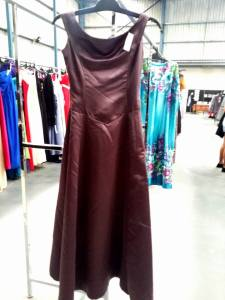 Understated yet elegant mocha coloured satin sleeveless gown, has a timeless boat neck, figure flattering lines & the very on trend